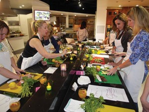 "Party goers learning knife skills at a Capers event. ""That was indeed super fun. Great friends, fun time and now I'm inspired to try cooking again.  Thanks, Bobbie for sharing your awesome cooking knowledge!"" -Stephanie Lauridsen Smith"