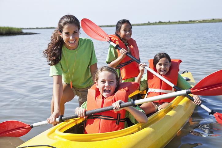 Teenage girl helping children in kayak