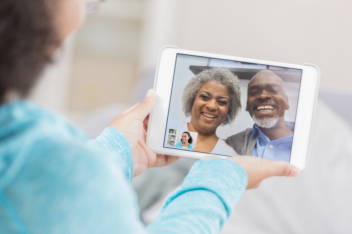 A senior couple laugh as they video chat from the screen of their unrecognizable granddaughter's digital tablet screen. She hold's the tablet with both hands.