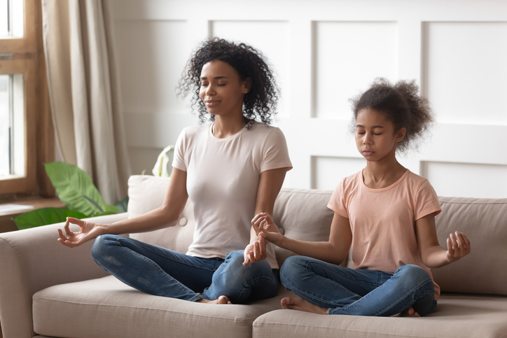 Happy mindful calm african american woman practicing yoga with healthy cute teenage daughter, teaching meditation in lotus pose and mudra gesture, relaxing together on couch in living room.