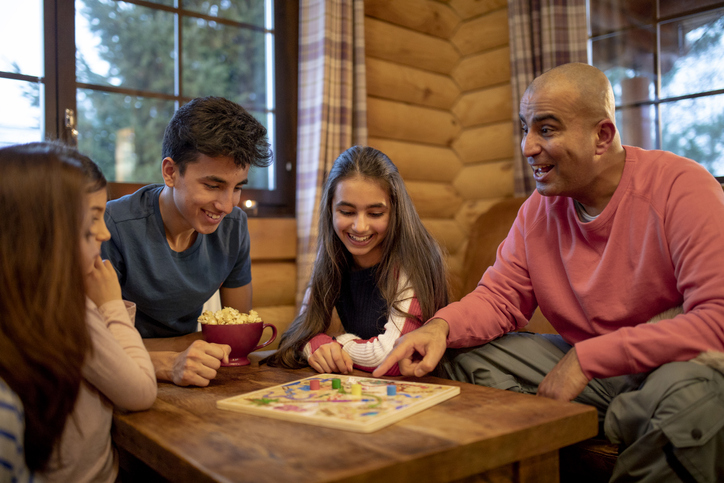 A family play a board game together in a log cabin. A mid adult man smiles and points at the game whilst talking to his daughter.