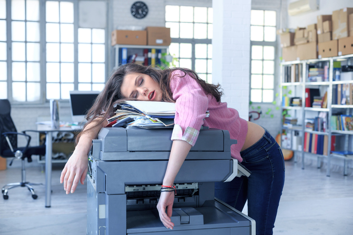 Tired young woman with messy hair sleeping on folders with documents and a copy machine, in the office. As background are tall windows, shelves with folders and boxes, and desk with computer and office chiars.