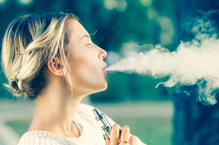 Teenage girl using electronic cigarette